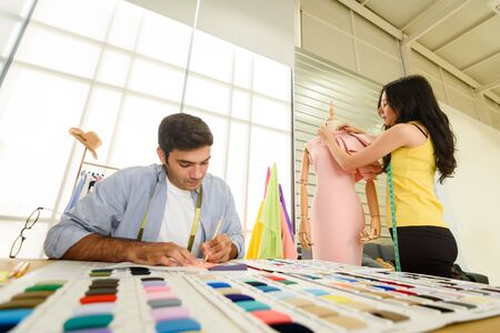 two designer working together on mannequin of new style of cloth