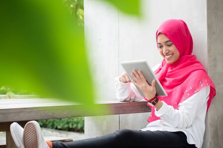 Smiling young muslim woman use tablet play social media wear pink hijab scarf with blur green foreground