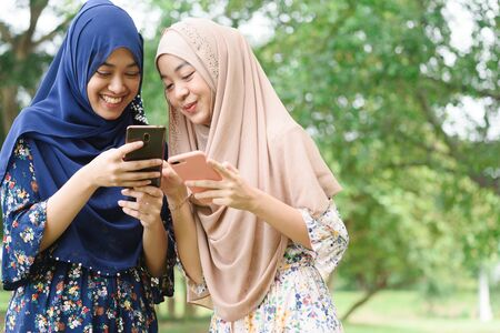Two muslim woman use smartphone play social media together, two islamic girl wear hijab head scarf