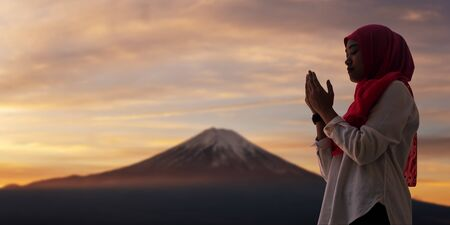 Silhoueitte of young muslim woman pray with beautiful sunset sunrise in background of Fuji mount