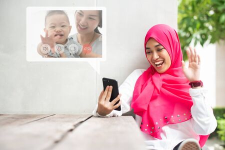 Young muslim woman make video call via her smartphone to her friends family