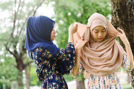 Two islamic girl help each other wear hijab head scarf 스톡 콘텐츠