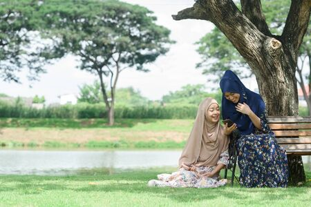 Two muslim teenage woman chill and relax in public park play social media on smartphone together