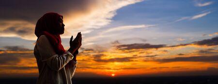 Silhoueitte der jungen muslimischen Frau beten mit schönem Sonnenuntergang/Sonnenaufgang im Hintergrund