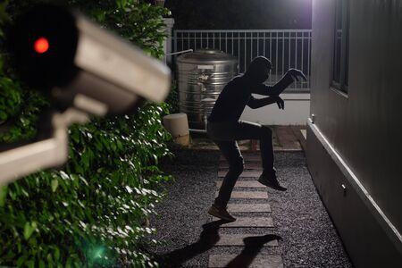 Un voleur saute d'un mur et pénètre dans une maison à la fenêtre, se faisant prendre par CCTV, caméra de surveillance Banque d'images