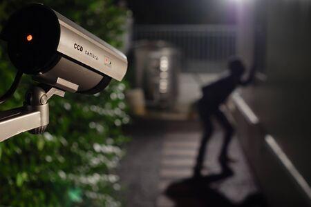 La caméra de surveillance CCTV fonctionne pendant la nuit, capture un voleur pendant qu'il pénètre par effraction dans une maison Banque d'images
