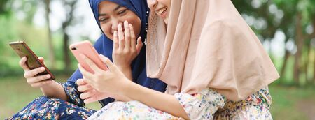 Two muslim woman use smartphone play social media together, close up hands of two islamic girl wear hijab head scarf