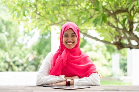 Smiling confidence young islamic woman sit on wooden table with smartphone and tablet wear pink hijab scarf