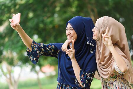 Two muslim woman use smartphone play social media together take selfie shot