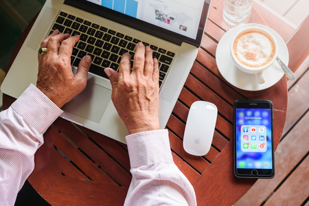 BANGKOK, THAILAND- 23th August 2019 : Old man hands work on Macbook pro with Iphone 7 plus with social media application icon of facebook, youtube, google search, instagram, twitter, linkedin, line whatsapp, and pinterest in a cafe