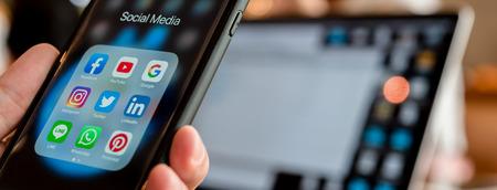 BANGKOK, THAILAND- 26 juni 2019: Handen van de mens gebruiken Iphone 7 plus met sociale media-applicatie van facebook, youtube, google search, instagram, twitter, linked in, line whatsapp en pinterest