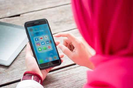 BANGKOK, THAILAND-10 augustus 2019: handen van islamitische vrouw gebruiken Iphone 7 plus met sociale media-applicatie van facebook, youtube, google search, instagram, twitter, linked in, line whatsapp en pinterest