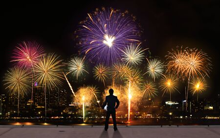 businessman stand on roof top of skyscrabber watching fireworks business success conceptual image