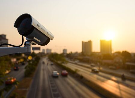 CCTV, Surveillance camera operating in city watching traffic road at sunset Banco de Imagens