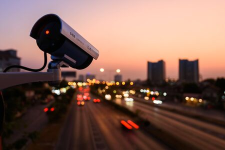 CCTV, Surveillance camera operating in city watching traffic road with beautiful twilight sky