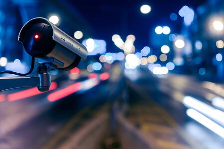 CCTV, Surveillance camera operating in city watching traffic road at night