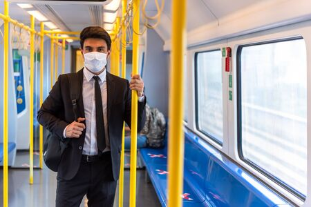 Businessman wearing white facial mask during travel by train, new normal life style during covid-19 pandemic with sign prohibitted people for social distancing on chair