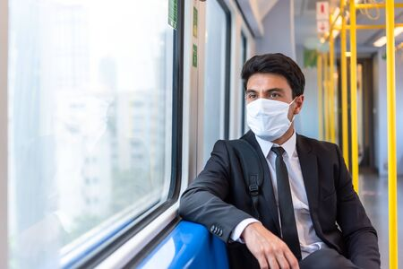 Businessman wearing white facial mask during travel by train sit near window, new normal life style during covid-19 pandemic with no people on train