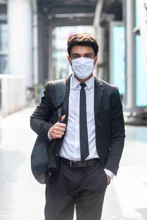 Businessman with sugical mask standing in an empty city during covid-19 outbreak