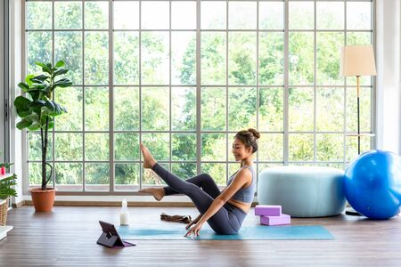Yoga student learning online from internet watching course from streaming at home