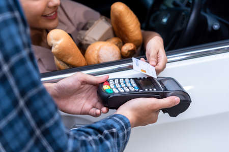 Drive thru service, woman buying fresh food product and pay with credit card without leaving the car Banco de Imagens