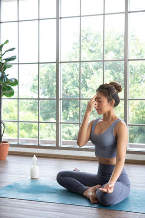 A Yoga performer meditating before start a yoga session at home 스톡 콘텐츠