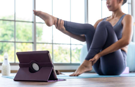 Asian woman practising yoga at home online use tablet attend online course