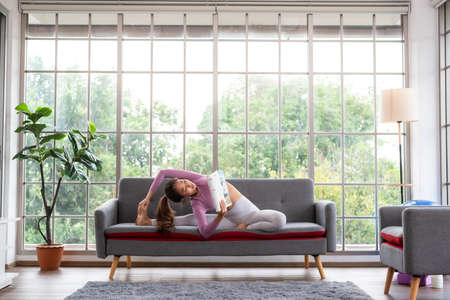 Young beautiful woman practicing yoga while reading magazine at home