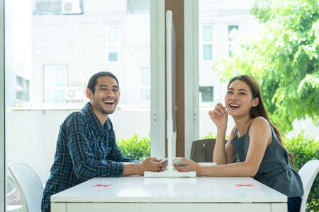 Two customer sit in restaurant with screen separate from each other prevent germs spread