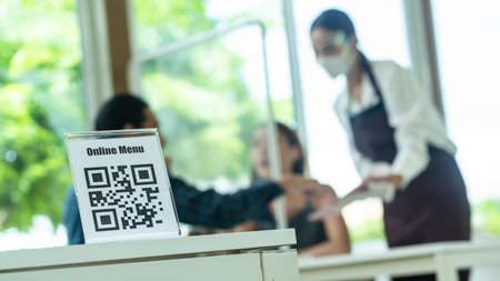 QR Code for online menu touchless activity in reopen restaurant with two customer and a staff in background