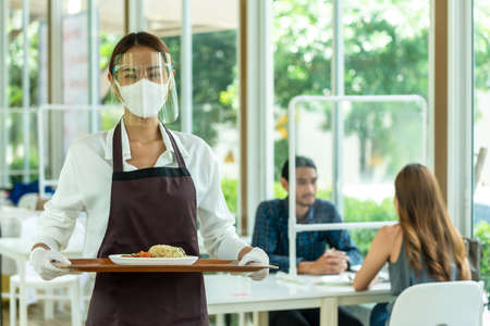 Restaurant staff serving food for customer in reopened restaurant in new normal style Stock fotó