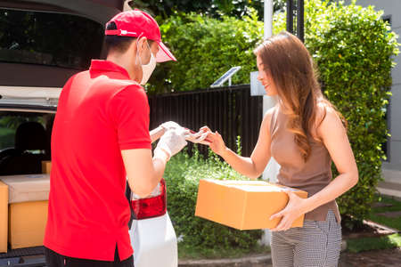 Delivery staff in red uniform delivering parcel to customer home sign on smartphone for recieve post box