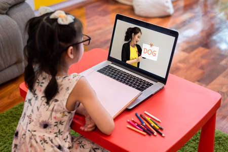Small little girl attending online class from home use laptop and internet for lock down period Stock fotó