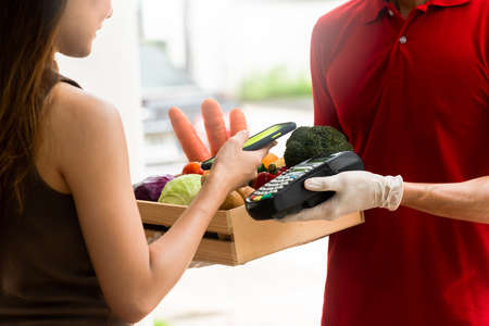 Delivery staff on red uniform holding box of fresh food delivering to customer's home and paid by online transaction use smartphone