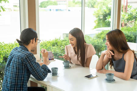 Three friends meet and see each other use smartphone play social media together in cafe
