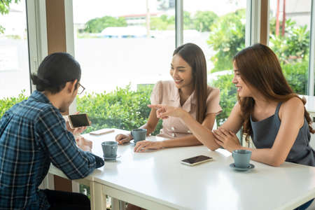 Three friends meet and see each other use smartphone play social media together Stock fotó