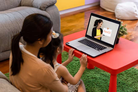 Mother and daughter sit in front of. a labtop study attending online course together at home