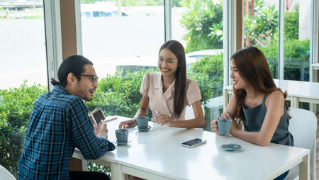 Three friends meet and see each other use smartphone play social media together Banco de Imagens