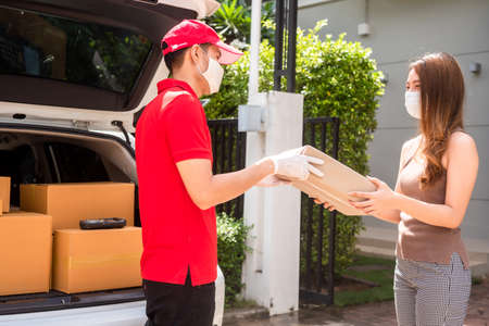 Delivery staff in red uniform delivering parcel to customer home