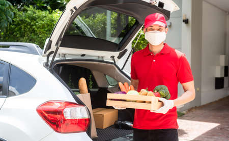 Delivery staff on red uniform holding box of fresh food delivering to customer's home