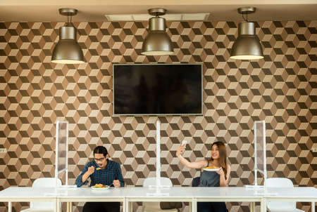 Man and woman in restaurant with plastic screen separate from each other for social distancing in new normal life style