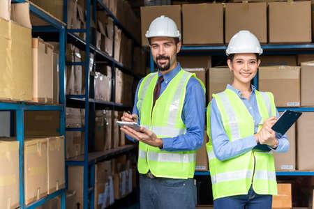 Senior boss working in warehouse with his secretary Banco de Imagens