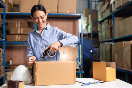 Warehouse worker packing a parcel box Banco de Imagens
