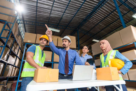 Warehouse management team working together in a large warehouse