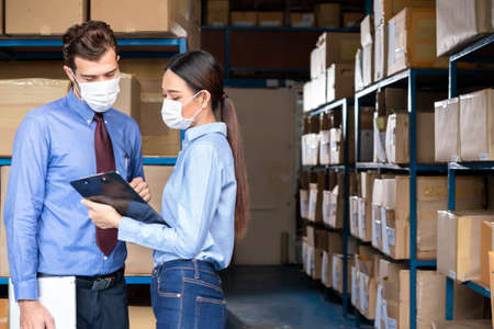 Two staff worker at warehouse wear surgical mask during work hour as new normal concept