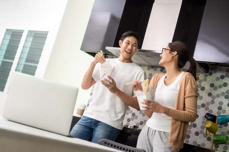 Asian couple having lunch at home by order delivery food Banco de Imagens
