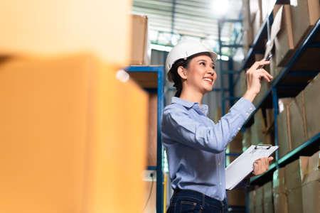 Asian female warehouse worker doing stock checking Banco de Imagens