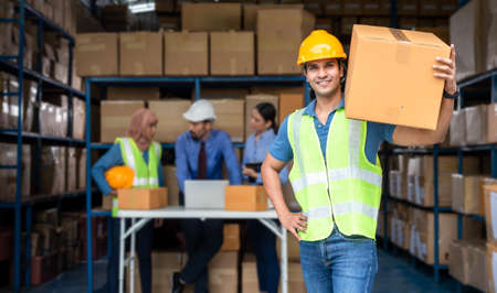 Warehouse worker holding a big parcel box working with his team
