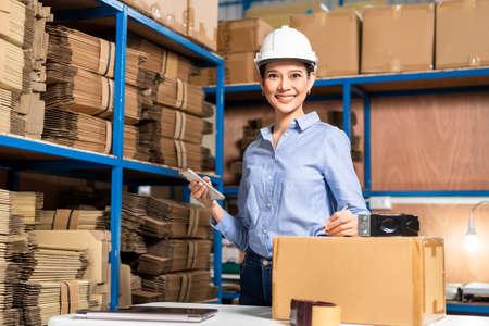 Warehouse worker wearing safety helmet using smartphone