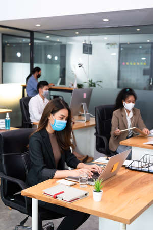asian Woman business worker working with laptop wearing flu mask in office show new normal lifestyle